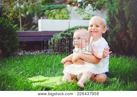 Happy Little Brother Playing Hugs His Sister Baby Sitting On Grass In A Green Garden, Concept Of Lov