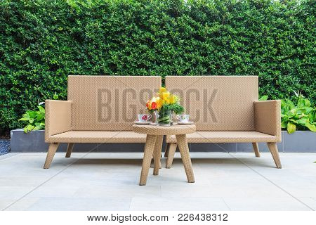 An Outdoor Interior Picture Of Two Resin Wicker Chair With Flower Bouquet In A Glass Vase And Tea Cu