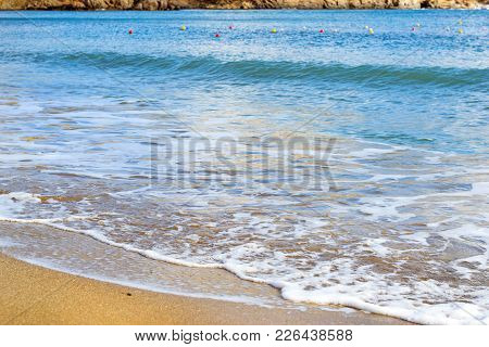 Surf And Tide Of Foamy Waves On A Sandy Beach. Sunny Sandy Livadi Beach In Sea Bay Of Resort Village
