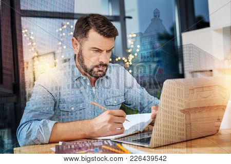 Frowning Man. Busy Serious Young Man Sitting In Front Of A Modern Convenient Laptop And Frowning Whi