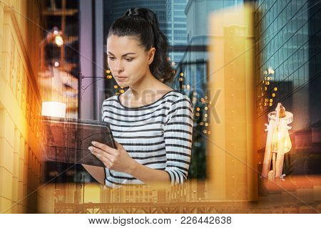 Serious Woman. Young Attentive Woman Feeling Worried While Sitting At Home With A Cup Of Tasty Coffe