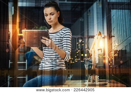 Smart Person. Strict Serious Young Woman Sitting On The Table In A Comfortable Room And Looking Atte