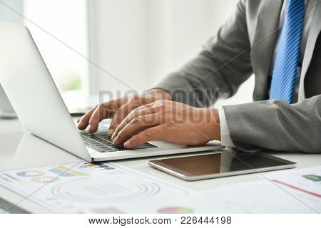 Businessman Hand Is Using A Laptop. Man In Grey Suit And Blue Necktie.
