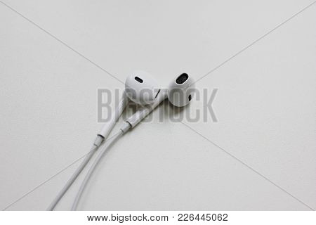 Moscow, Russia - February 9, 2018: Apple Air Pods White Headphones Isolated On Table. Music Listenin
