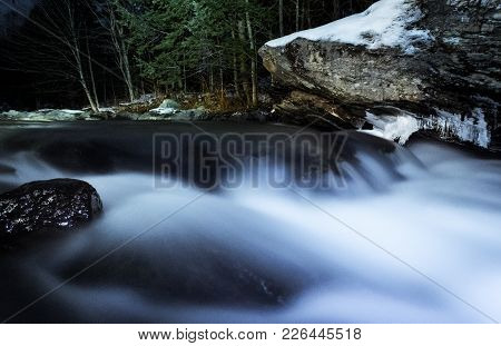 Long Exposure Of River At Night In Sutton, Quebec, Canada. Rocks And Forest On Background
