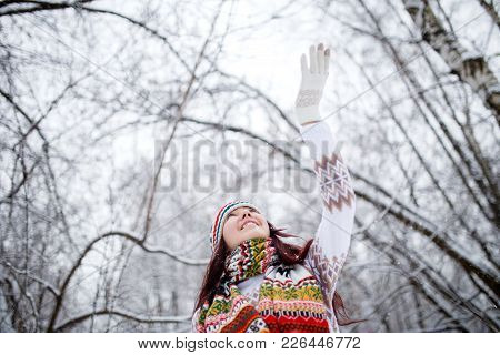 Photo Of Smiling Brunette Looking Up In Knitted Hat And Scarf Catching Snowflakes In Winter Forest D
