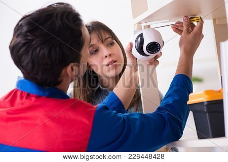 Client getting securty camera installed at home by contractor