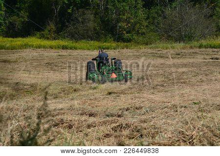 A Farmer Raking Cutting And Bailing His Hay Field