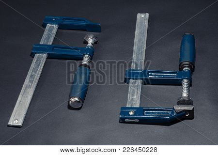 Joiner Or Carpenter Clamps On The Table. Close-up.