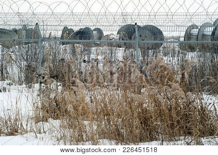 Electrified Fence Of The Exclusion Zone With Empty Coils From The High-voltage Cable Behind It, With