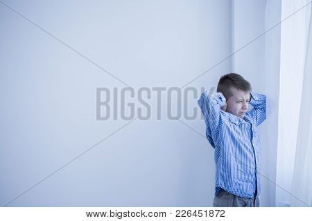 Young Autistic Boy In A White, Empty Room Standing Next To A Window Covering His Ears