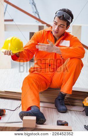 Carpenter wearing yellow hardhat in contractor workshop