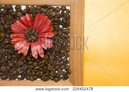 Wooden Photo Frame Filled With Coffee Beans And A Red Flower, Top View, Yellow Background, Copy Spac