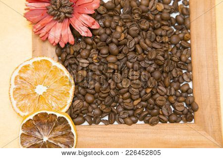 Wooden Photo Frame Filled With Coffee Beans, Orange Slices And A Red Flower, Top View, Yellow Backgr