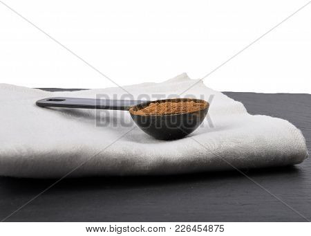 Colorful And Crisp Image Of Carob Powder In Measuring Spoon On Shale