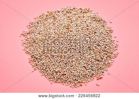 a small pile  of organic white chia seeds rich in omega-3 fatty acids, top view on a pink background
