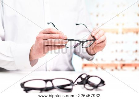 Optician In Store Holding Glasses. Eye Doctor With Lenses. Professional Optometrist In White Coat Wi
