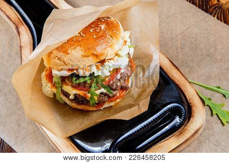 Home Made Hamburger With Beef, Onion, Tomato, Lettuce And Cheese. Fresh Burger Closeup On Wooden Rus