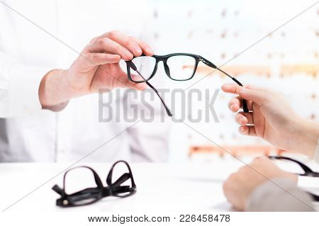 Optician Giving New Glasses To Customer For Testing And Trying. Eye Doctor With Client Comparing Spe