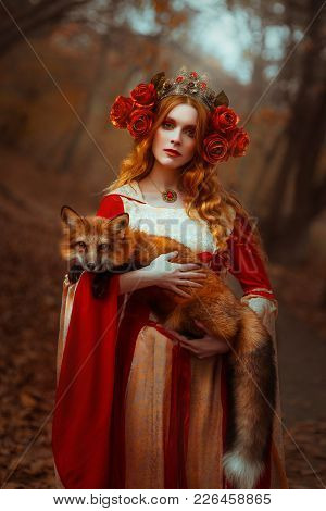 A Young Woman In Medieval Red Dress With A Fox