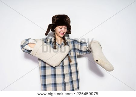 Funny Young Girl In A Hat With Ear-flaps Holds Warm Felt Boots In Hands