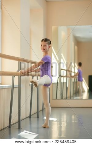 Beautiful Young Ballerina In Ballet Studio. Cute Young Girl Training Near Barre In Ballet Hall. Ball