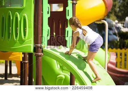 Little Caucasian Girlie Climbing On Jungle Gym, Sunny Summer Day, Recreation Concept