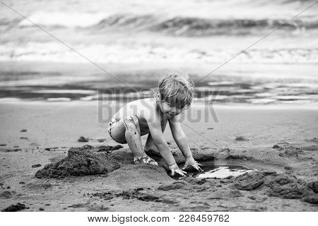 Cute Muddy Baby Boy With Blond Hair Ponytail In Trunks Plays With Wet Sand On Sandy Beach On Sunny S