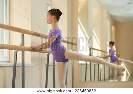 Young Ballerina Doing Exercise In Studio. Cute Girl Training Near Barre At Ballet Hall. Go To Your D