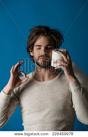 Sleepy Man With Disheveled Hair Hold Toilet Paper And Show Ok Gesture In Underwear On Blue Backgroun