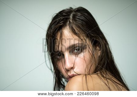Girl With Makeup Face Skin And Naked Shoulders. Woman With Wet, Oily Hair On Grey Background. Skinca