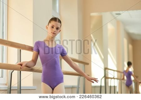 Pretty Young Ballerina Near Barre. Beautiful Young Girl Standing Near Railing At Ballet Hall And Loo