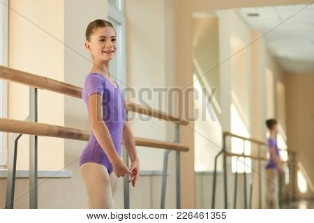 Happy Young Ballerina At Class. Beautiful Young Smiling Ballet-dancer Standing Near Barre At Ballet
