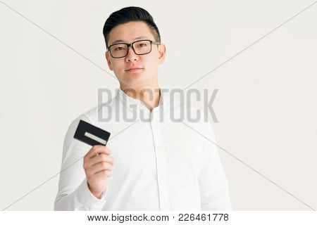 Confident Korean Businessman Using Credit Card To Pay Bills. Serious Successful Young Male Entrepren