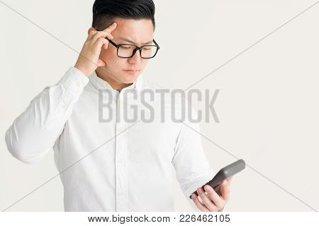 Confused Asian Businessman Using Calculator And Concentrated On Figures. Thoughtful Young Male Accou