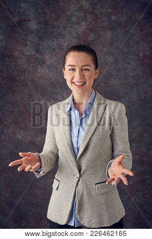 Smart smiling young professional or business woman pointing her finger in the air with a pleased smi