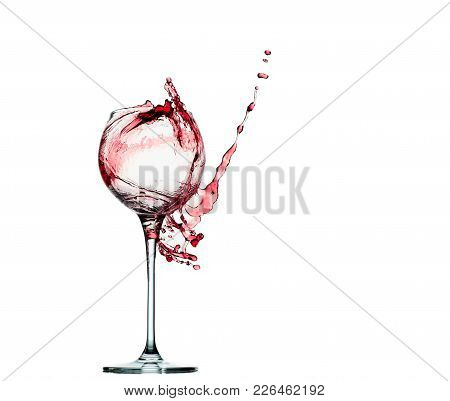 Pouring Red Wine In Glass Goblet Isolated On White.