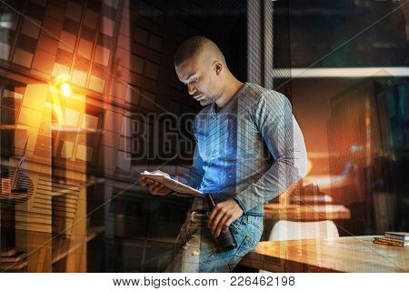 Concentrated Reading. Calm Attentive Young Man Looking Concentrated While Standing Next To The Table