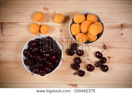 Bowls With Fresh Apricots And Cherries Berries On Wooden Background. Top View.