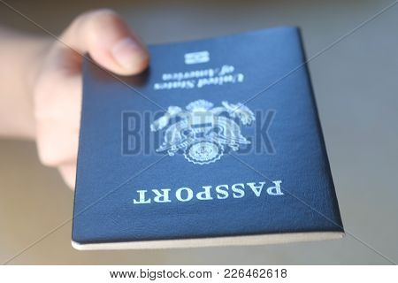 Persons Hand Holding And Giving Passport Of United States