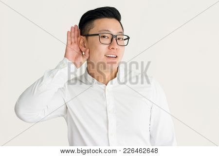 Curious Asian Employee Eavesdropping Colleagues Talk And Holding Hand Near Ear To Concentrate On Inf