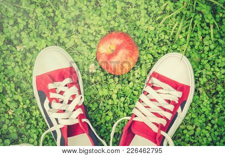 Sports Shoes And Red Apple On Green Grass. Top View.