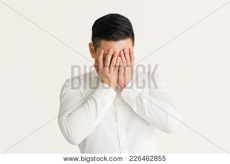 Depressed Man Crying And Covering Face With Hands Against White Background. Sad Young Businessman Su
