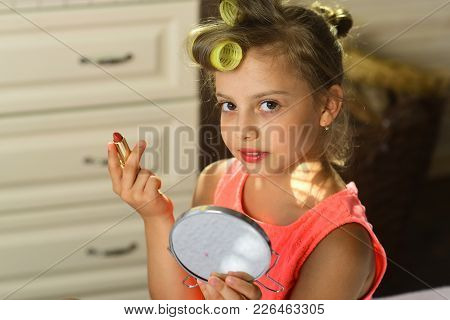 Child Sits On Bed With Pink Lipstick And Mirror. Little Girl With Curlers And Cheerful Face Wears Fa