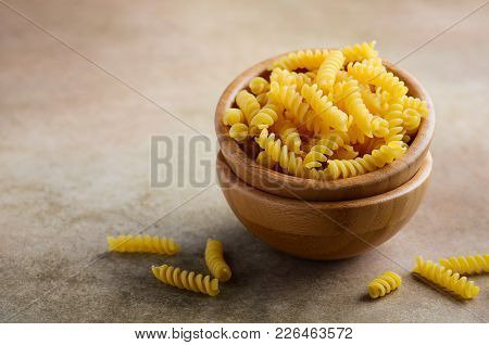 Raw Fusilli Pasta In A Wooden Bowl, Selective Focus, Copy Space.