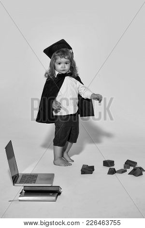 Small Boy Child With Long Blond Hair In Blue Shirt Black Graduation Gown And Cap Playing With Wooden