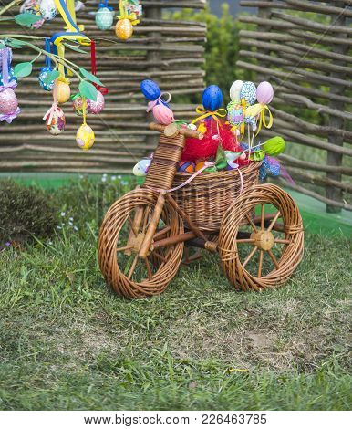 Small Bicycle With Easter Eggs. Wicker Tricycle With Basket On Grass. Happy Easter Celebration. Spri
