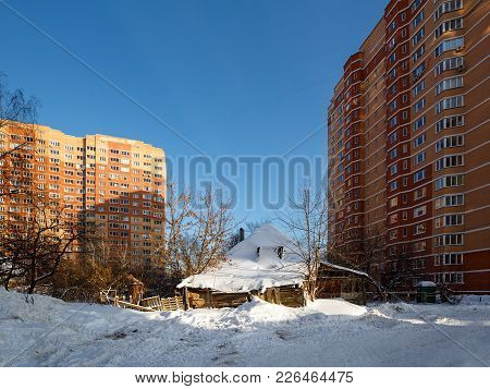 The Old Rickety Wooden House In The Courtyard Of The New High-rise Residential Buildings. City Of Ba