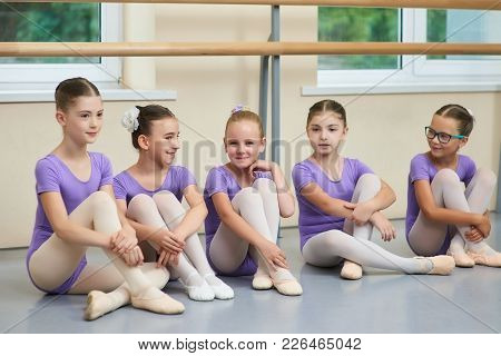 Young Ballerinas Sitting On The Floor. Group Of Young Cute Ballet Dancers Having Rest Between Rehear