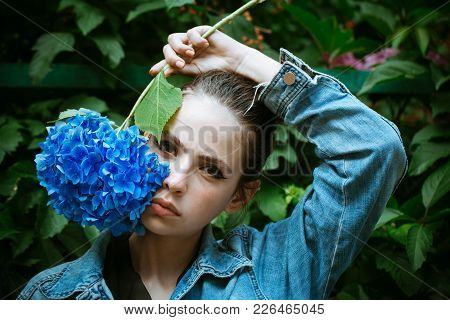 Woman Hold Blue Hydrangea At Makeup Face. Girl With Healthy Skin And Flower. Skincare, Visage, Spa.